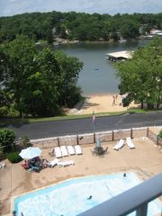 Osage Beach condo photo - The deck overlooks the pool and sandy beach playground and lake swimming area