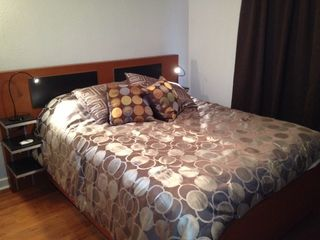 Austin house photo - Here's the comfy queen size bed with blackout drapes and handy reading lights.