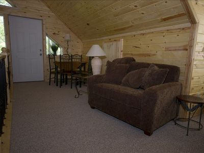 Living area with one of two twin sleeper beds, game table ,and door to upper dec
