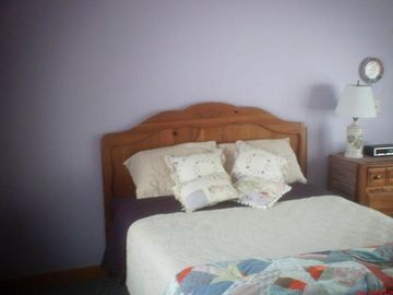Large bedroom with queen bed and bunk beds. Small table with 2 chairs.