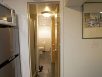 Long bathroom, shower on left, toilet visible in back