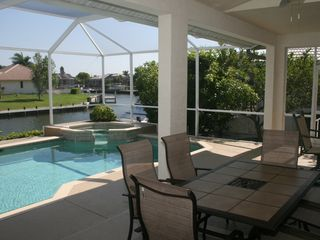 Vacation Homes in Marco Island house photo - Dine outdoors poolside on the spacious lanai. Areas in sun and under cover.