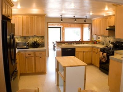 Open kitchen with new appliances, gas range, and river views