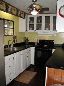 Kitchen includes a dishwasher and glass topped electric range.