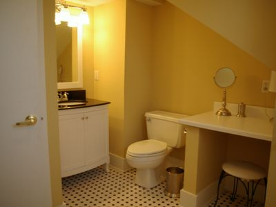 2nd floor full size bathroom with enclosed tub, tile floor and makeup area.