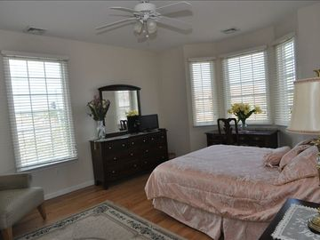 large bedroom with queen bed and extra seating for reading, etc