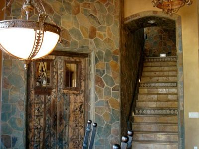 Old world door leading into kitchen.  Stairway leading to wine room and patio