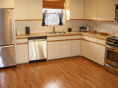 The large kitchen features stainless appliances & connects to the laundry room.