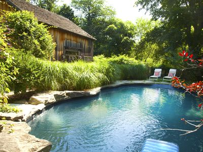 The pool is in a natural, very private setting with designer (DWR) teak chaises.