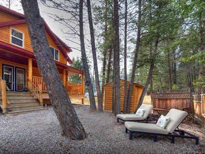 Private backyard area bordering a forested reserve, lounge chairs and a hammock