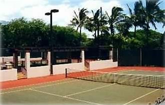 Two separated, free, lighted tennis courts with practice backboard