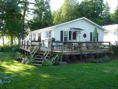 Exterior view of cottage and wraparound deck on the lake.