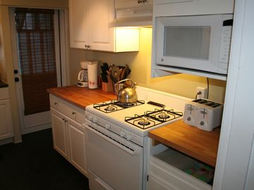 View of gas stove, oven, microwave, toaster & coffee maker.