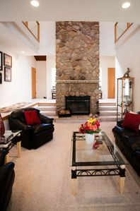 Sunken living room with floor to ceiling rock woodburning fireplace