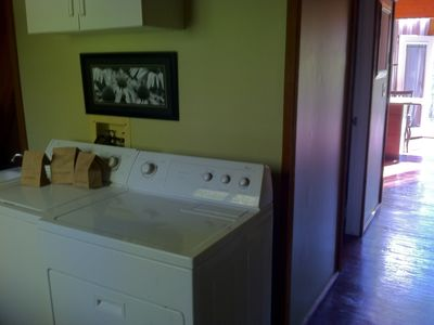 Laundry room includes utility sink, iron/iron. board, storage cabinets