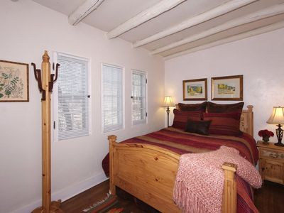 Bedroom with queen bed, luxury linens, ceiling vigas, wood floors, original art