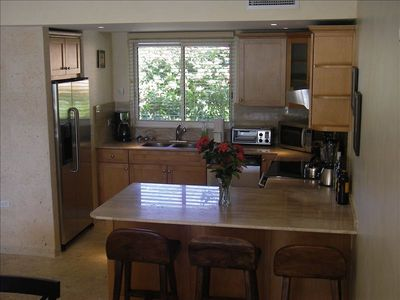 Kitchen with stainless steel appliances & breakfast bar area including 3 stools
