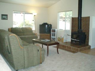 Tulloch Lake house photo - Living Room Off the Kitchen with Wood Stove and TV Looking South