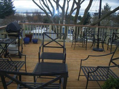 Large deck with gas barbeque, cocktail, and eating table, looking west to sunset