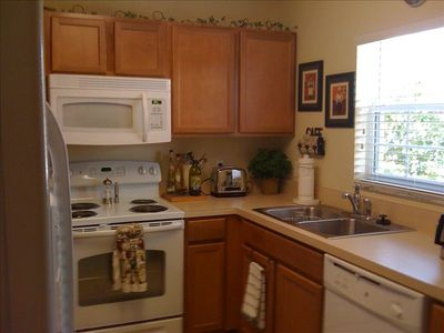Fully Stocked kitchen with dishwasher and side by side fridge with icemaker.