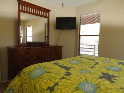 Master bedroom is bright and has a flat screen TV.