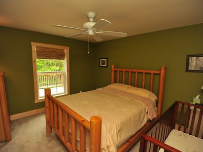 2nd bedroom on main floor with queen bed and crib.
