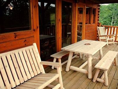 The deck features a picnic table and rockers