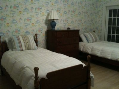 Guest room with matching twins plus twin boat bed with trundle. Opens to deck.