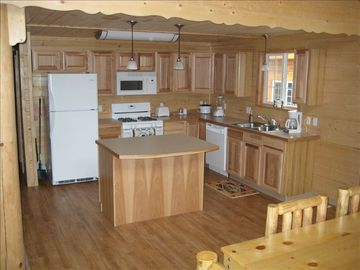 Fully furnished kitchen with dishwasher, stove, microwave and refrigerator.