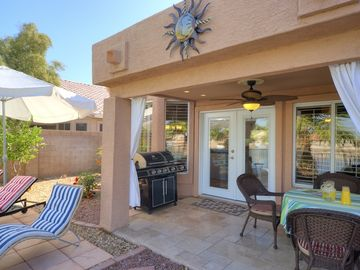 Back patio areas with patio table, chairs, BBQ, and loungers under the umbrella.