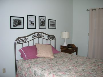 One of the master bedrooms with queen bed and local photography.