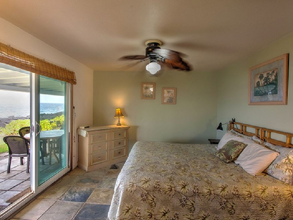 Master bedroom with king bed, sliders to oceanfront lanai and hot tub