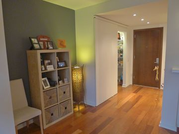 Hallway includes nook and hardwood floors with coat cupboard and kitchen pantry