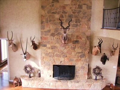 Grand front room showcases African animal mounts and a soaring stone fireplace.