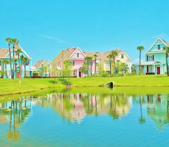 Colorful pastel Key West-style villas surround lagoon.