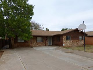 Lubbock house photo - Front of home with lone oak tree... and basketball court!