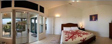 Panoramic Shot of Master Bedroom with King Size Bed and TV. Patio Doors to Lanai