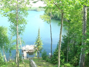 View of the lake, dock, and pontoon boat from the house.