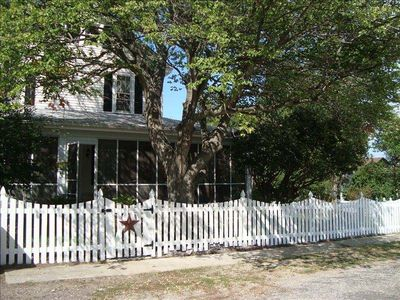 White picket fence with wraparound screened porch