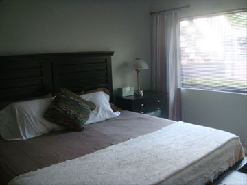 King sized master bedroom with flat screen wall-mounted TV