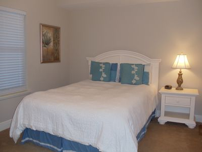 Guest bedroom with queen size bed and flat panel TV.
