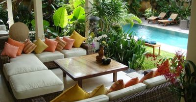 Comfy open outdoor living room surrounded by gardens and pools