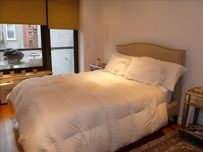 Master bedroom has a balcony and queen size bed with luxury hotel bedding