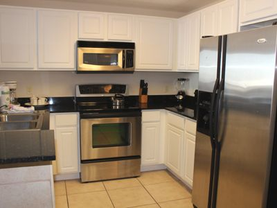 Kitchen with stainless steel appliances, granite countertops, & ceran top stove