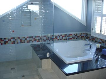 Master Bathroom has large soaker tub and rainfall shower with view of Point Dume