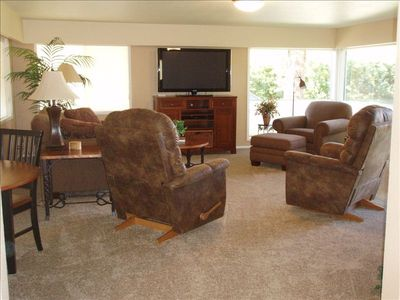 Cozy living room with large picture windows. La-Z-Boy recliners.
