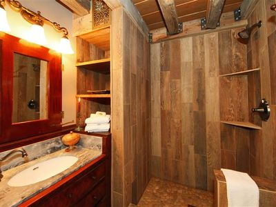 rustic bathroom with wood tiled shower and antique dry sink
