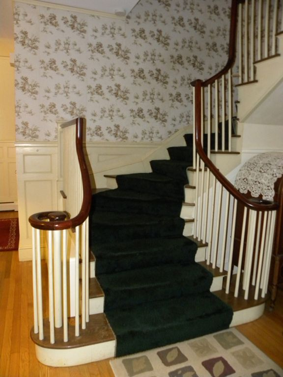 Stairway to three ensuite bedrooms, all w/sofas, TV's, DVD's, & two with decks.