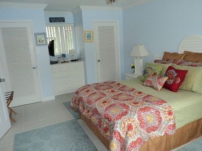bedroom with his & her closets, wall mounted flat screen TV and chair.....