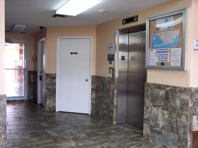 Seacrest Lobby with two elevators; back doorway to beachside pool and boardwalk